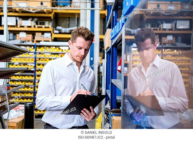 Male factory manager writing on clipboard in factory warehouse