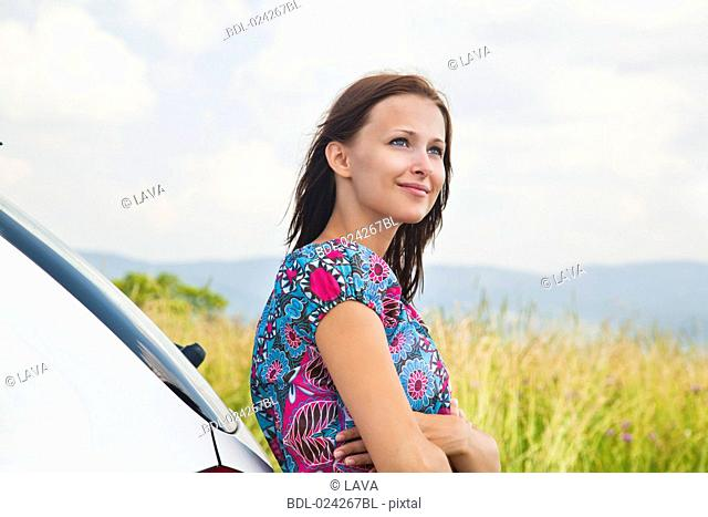portrait of young woman leaning against car