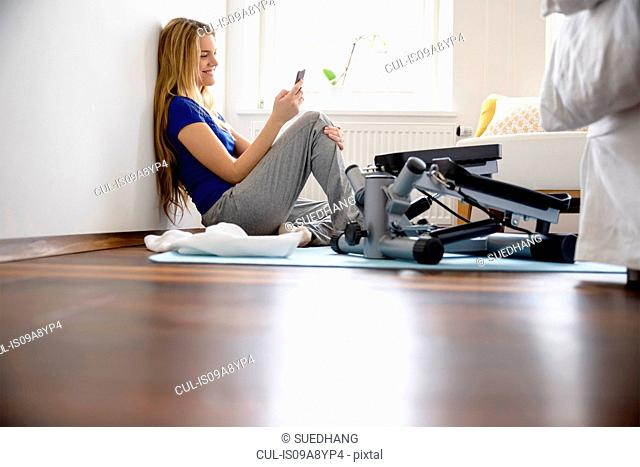 Young woman sitting on bedroom floor looking at smartphone
