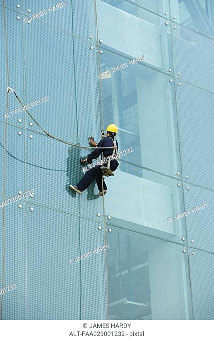 Window washer on side of office building, close-up