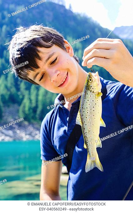 teen ager fisherman shows happy, catching a brown trout, Salmo trutta fario, in an alpine lake