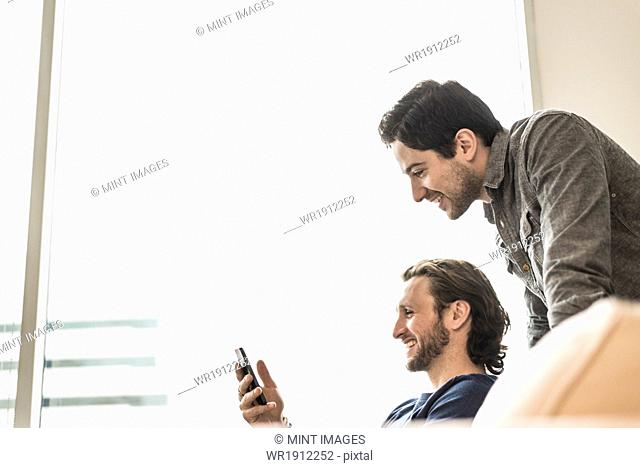 Two business men looking at a smart phone and smiling