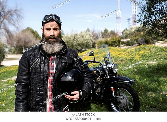 Portrait of biker standing on a meadow in front of his motorcycle