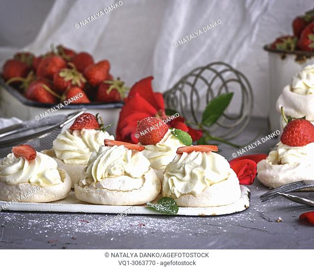baked meringue with cream and fresh strawberries, behind the tray with red berries