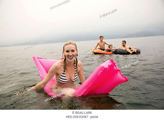 Portrait smiling woman on pool raft in lake
