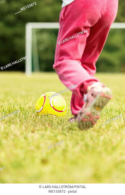 Girl in pink pants playing soccer, kicking a yellow football in front of goal