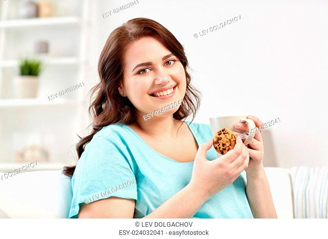 people, junk food, unhealthy eating and leisure concept - happy plus size young woman with cup of tea with cookie at home