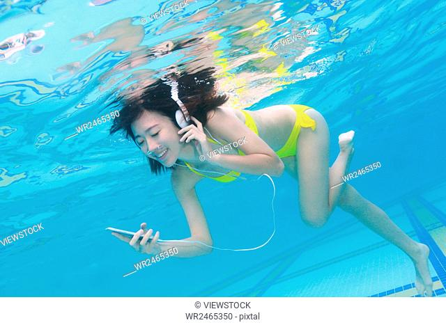 Young woman listening to music under the water