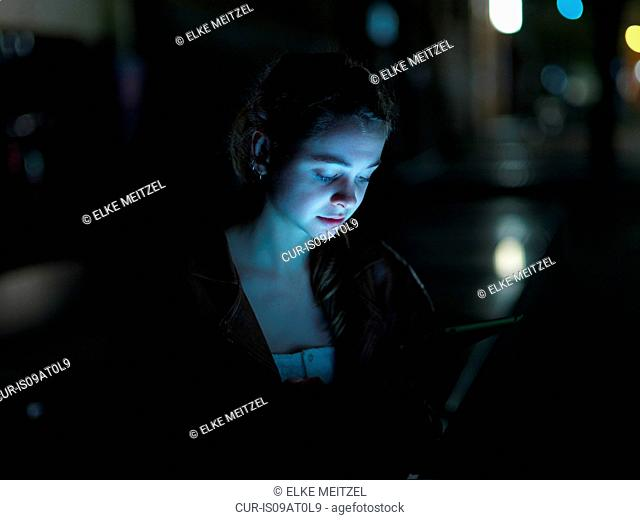Young woman using digital tablet, outdoors, at night, face illuminated
