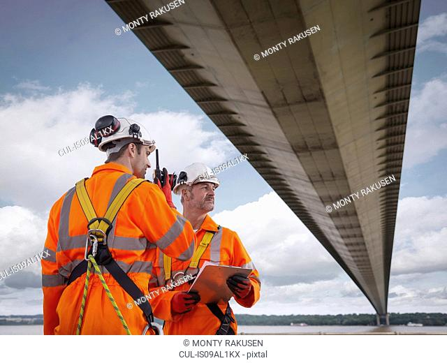 Bridge workers using walkie-talkie under suspension bridge. The Humber Bridge, UK was built in 1981 and at the time was the world's largest single-span...