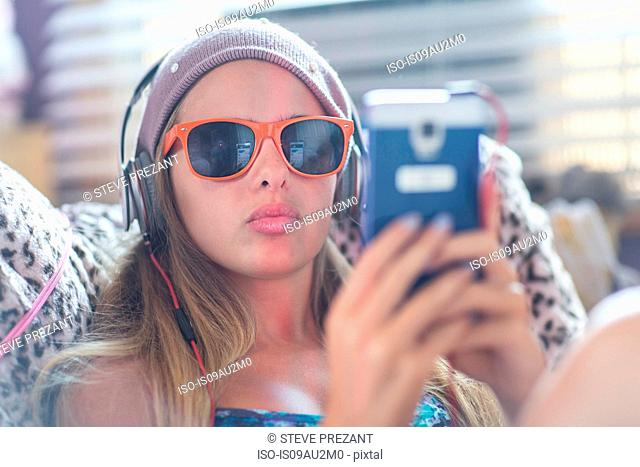 Teenager with sun glasses using smartphone on lazy chair