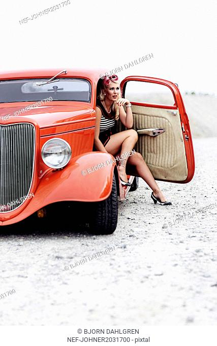 Woman wearing retro clothes sitting in vintage car