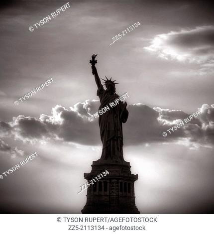 sihouette of the statue of liberty with clouds