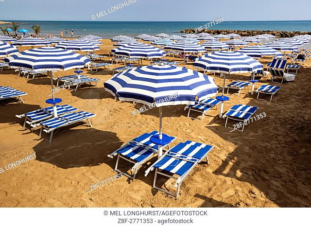 Sun umbrellas and sun beds on a beach, Marina Di Ragusa, Sicily, Italy