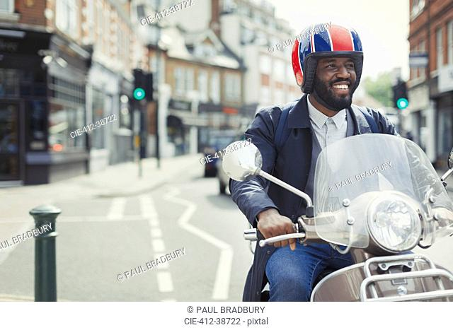 Smiling young businessman in helmet riding motor scooter on urban street