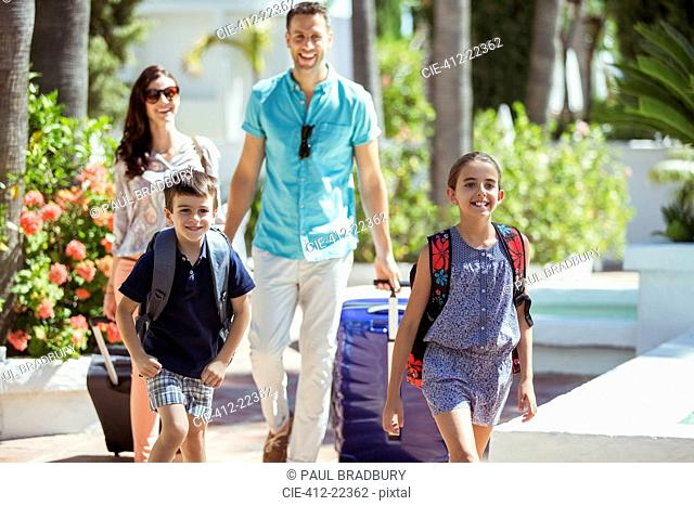 Family with suitcases walking towards tourist resort