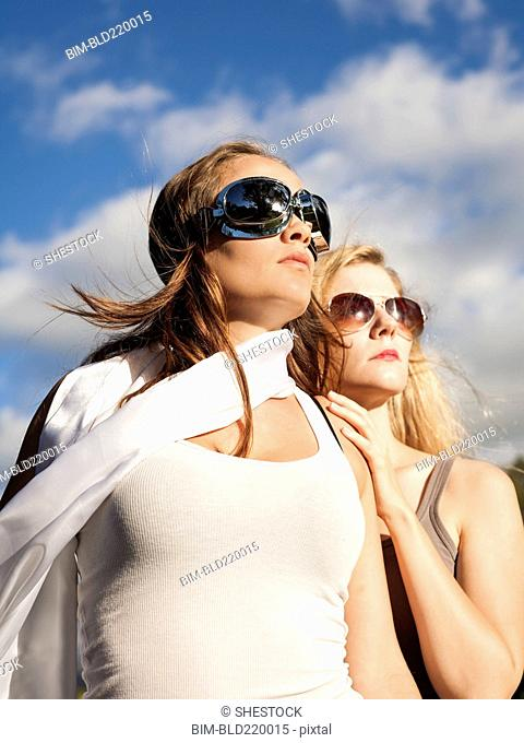 Caucasian women wearing sunglasses and looking up