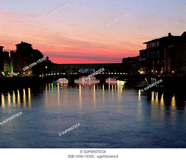 Silhouette of a bridge across a river lit up at dusk, Ponte Vecchio, Florence, Italy
