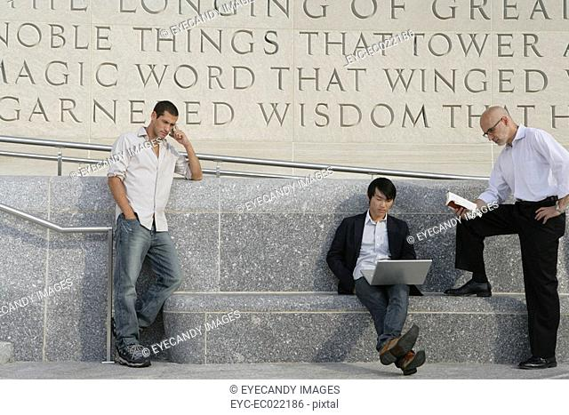 group of multi ethnic men outside on phone laptop and reading a book