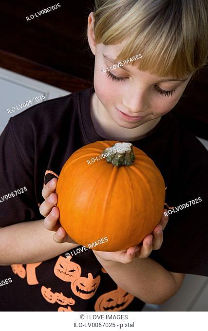 Little girl holding an orange Hallowe'en pumpkin