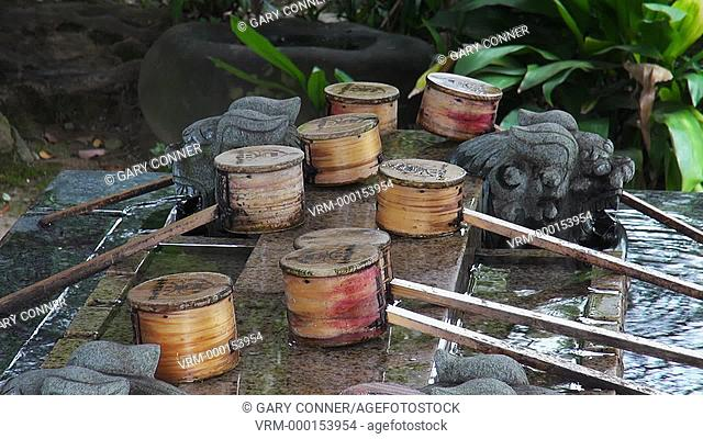 Purifying basin and dippers at a shrine in Hitoyoshi, Japan. Water-filled basins, called chozubachi, are used by worshippers for washing their hands and mouth...
