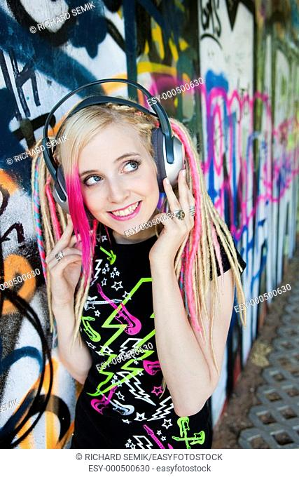 portrait of young woman with headphones at graffitti wall