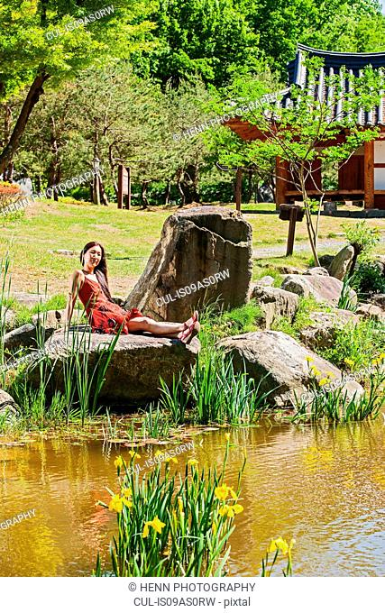 Woman relaxing at a pond in Damyang cultural village, South Korea