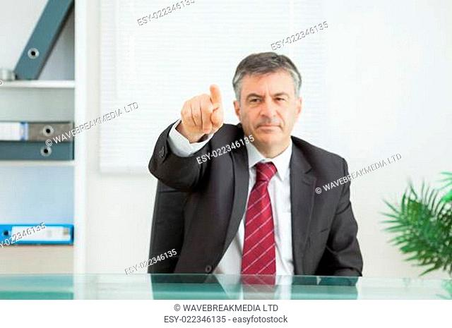 Business man pointing seriously in his office