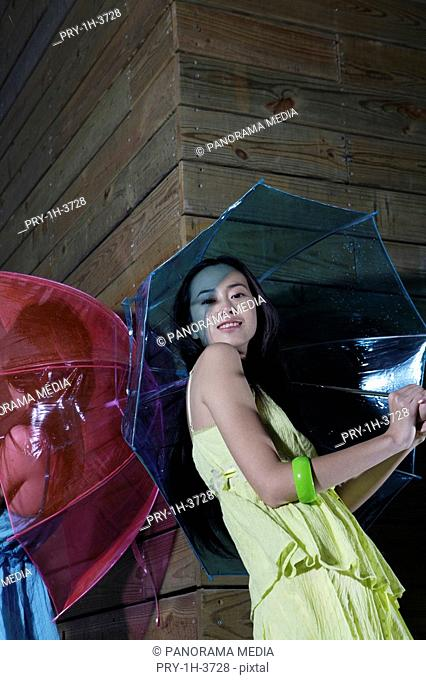 Portrait of a young women holding umbrella by building exterior