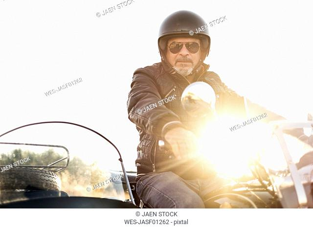 Portrait of cool biker wearing helmet and sunglasses on his sidecar motorcycle at backlight