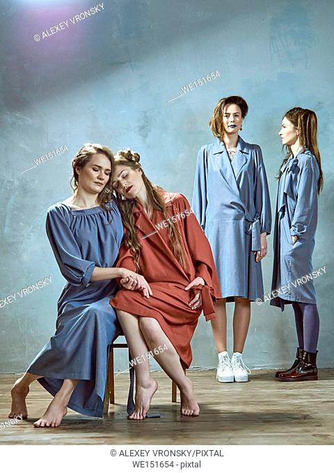 Photographing fashion collections of clothes in the Studio. Photos were taken opposite the dark gray walls. Four young girls dressed in long dresses