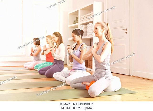 Group of women in yoga studio sitting in Lotus pose
