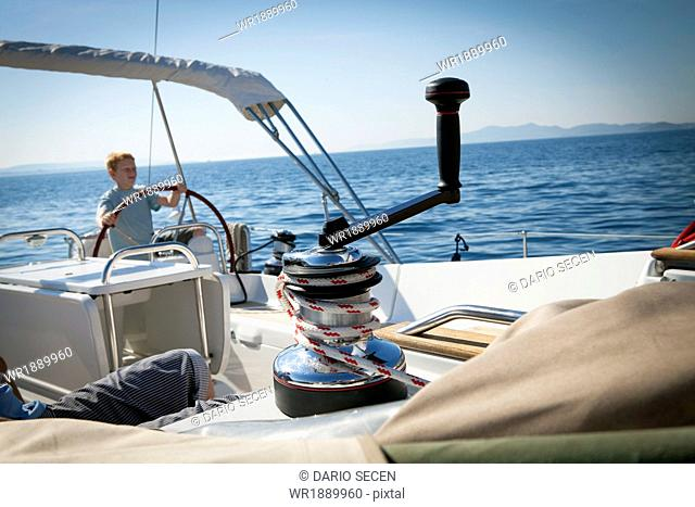Boy on sailboat, stands at wheel, Adriatic Sea, Croatai