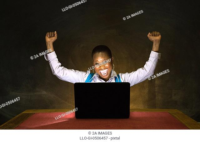 A woman raise arms in happiness whist looking at computer screen in Johannesburg, Gauteng, South Africa