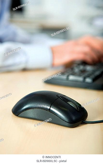 Office worker using computer, mouse in foreground
