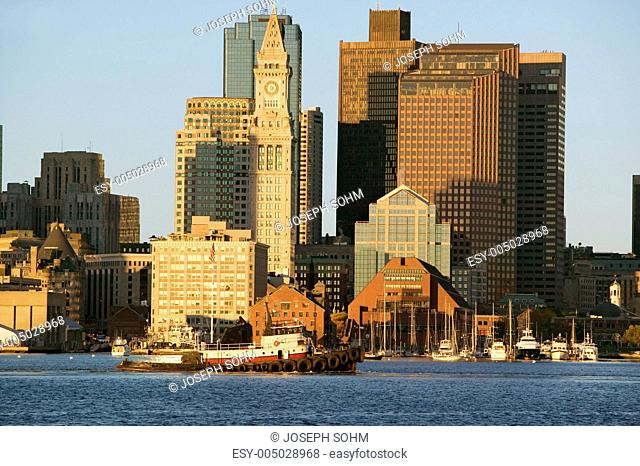 Tugboat with Boston Harbor and the Boston skyline at sunrise as seen from South Boston, Massachusetts, New England