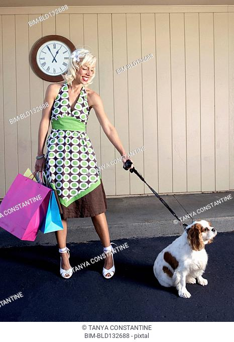 Caucasian woman with dog on sidewalk