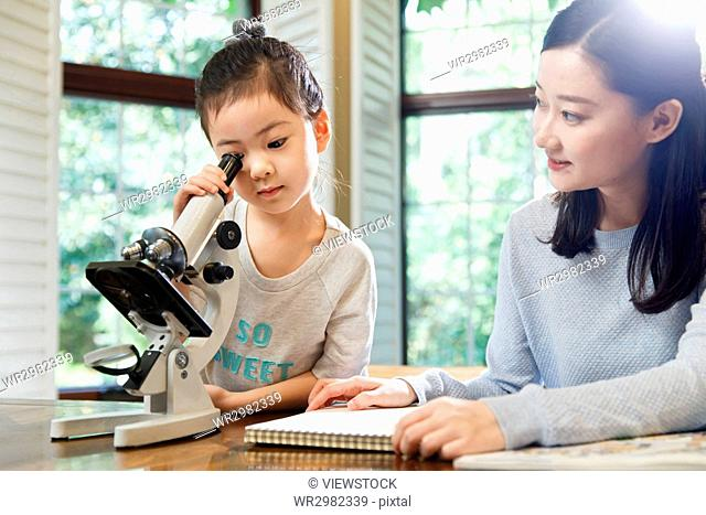 Mother and daughter using microscope