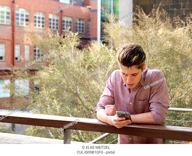 Young man leaning on fence, using smartphone, outdoors