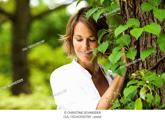 woman next to a tree smiling