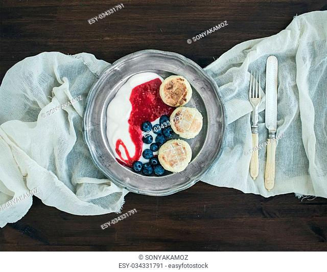 Breakfast set: curd pancakes with yogurt, fresh blueberry and raspberry jam on a vintage metal plate on a piece of white linen fabric over a dark wood...