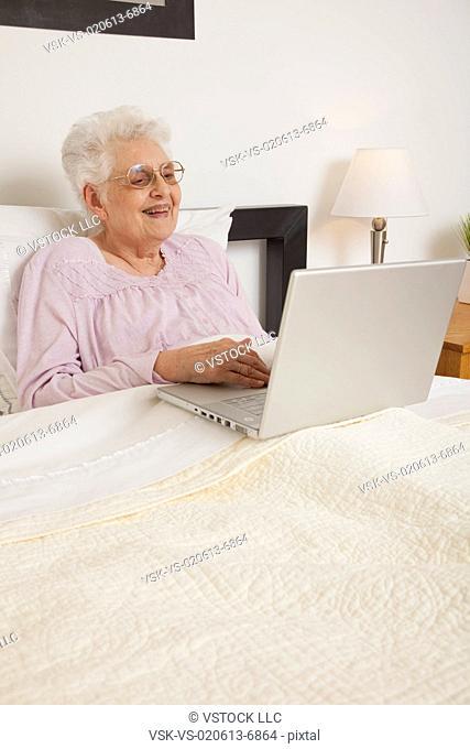Senior woman in bed, using laptop