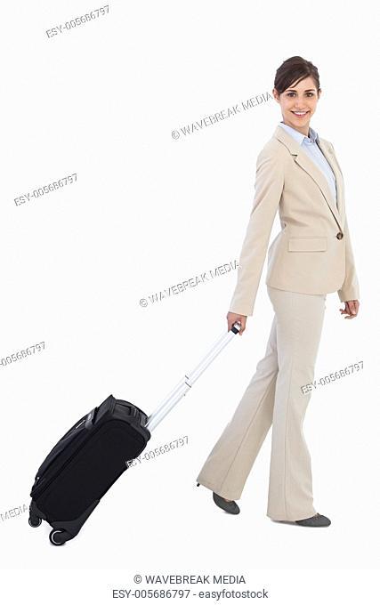 Smiling businesswoman pulling suitcase