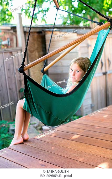 Portrait of girl looking over her shoulder from porch swing chair