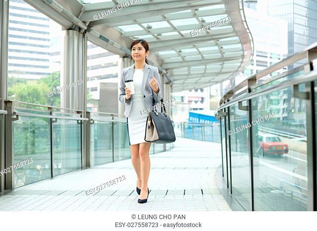 Business woman walking drinking coffe