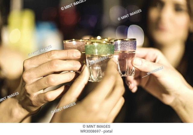 A group at a party holding shot glasses and celebrating