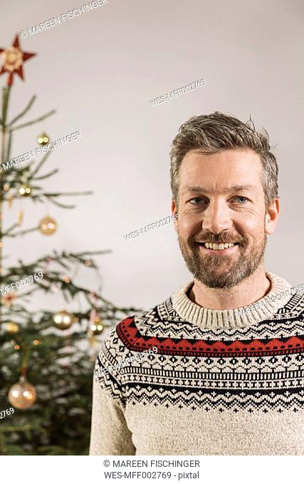 Portrait of man in front of Christmas tree