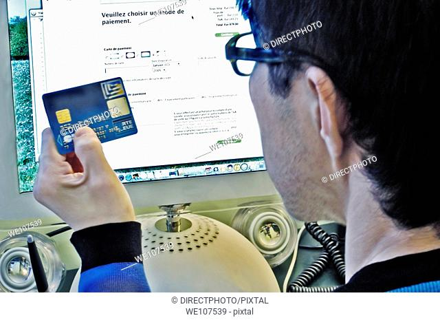 Portrait, Young Asian Man Making Purchase online from Intenet Web site with Credit Card