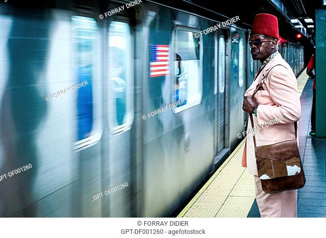 NEW YORKER WEARING A FEZ ON A NY SUBWAY STATION PLATFORM, FASHION, OFF-BEAT, MANHATTAN, NEW YORK CITY, STATE OF NEW YORK, UNITED STATES, USA