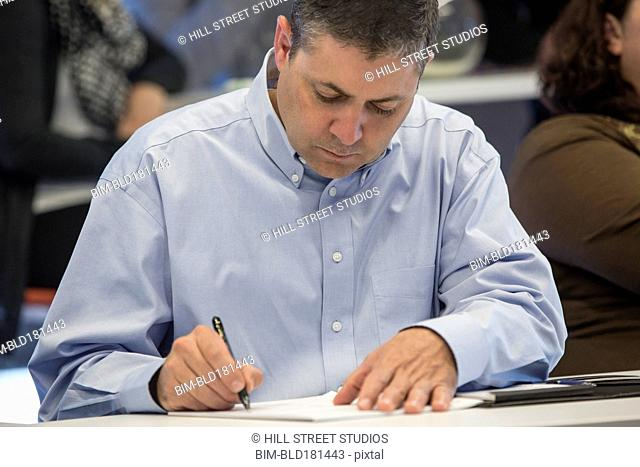 Businessman writing notes in office meeting